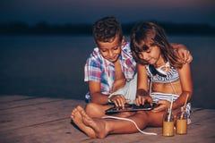 Enfants jouant avec le comprimé numérique sur le pilier en bois photos stock