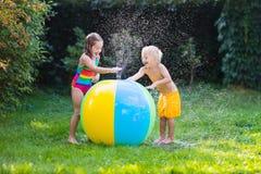 Enfants jouant avec le jouet de boule de l'eau Photographie stock libre de droits