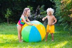 Enfants jouant avec le jouet de boule de l'eau Photo libre de droits