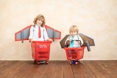 Enfants jouant avec le paquet de jet à la maison photos stock