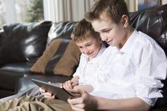 Enfants jouant avec le PC de comprimé Photos stock
