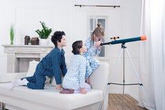 Enfants jouant avec le télescope et regardant la fenêtre Photographie stock libre de droits