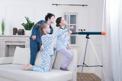 Enfants jouant avec le télescope et regardant la fenêtre Photo libre de droits