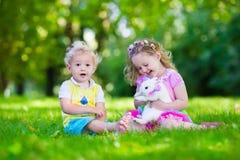 Enfants jouant avec le vrai lapin Image stock