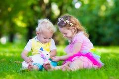 Enfants jouant avec le vrai lapin Photographie stock libre de droits