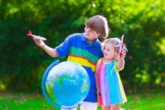 Enfants jouant avec les avions et le globe dans un jardin Images stock