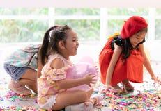Enfants jouant avec les ballons et le papier de lancement en partie d'enfant photographie stock