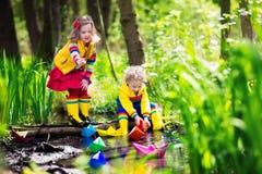 Enfants jouant avec les bateaux de papier colorés en parc Photos stock