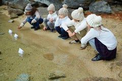 Enfants jouant avec les bateaux de papier sur le lac Photos stock