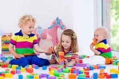 Enfants jouant avec les blocs colorés de jouet Photos libres de droits