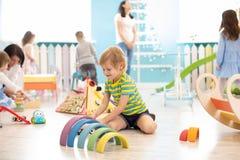 Enfants jouant avec les blocs colorés Jouets éducatifs de jardin d'enfants photo stock