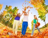 Enfants jouant avec les feuilles jetées dans la forêt Photos libres de droits