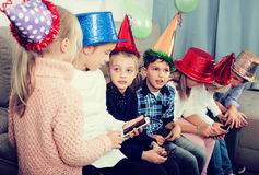 Enfants jouant avec leurs smartphones ensemble Photographie stock libre de droits