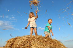 Enfants jouant avec un foin, une paille de blé sur une meule de foin Image stock