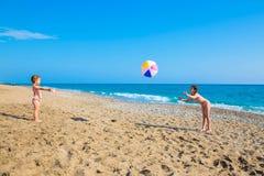 Enfants jouant avec une grande boule sur la plage Photographie stock libre de droits