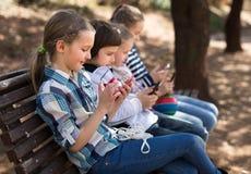 Enfants jouant dans des smartphones sur un banc de rue Photos stock