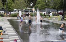 Enfants jouant dans la fontaine de parc de terriers de Klyde Photographie stock libre de droits