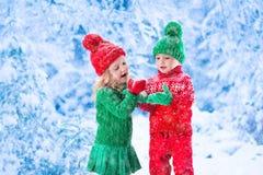 Enfants jouant dans la forêt neigeuse d'hiver Photographie stock
