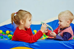 Enfants jouant dans la piscine avec des boules Photographie stock