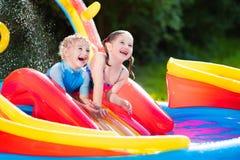 Enfants jouant dans la piscine gonflable Image libre de droits