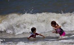 Enfants jouant dans le grand ressac Image libre de droits