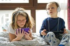 Enfants jouant dans le lit avec leurs comprimés et téléphones Image stock