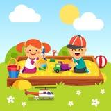 Enfants jouant dans le puits de sable de jardin d'enfants Photographie stock