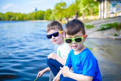 Enfants jouant dehors en nature : se reposer sur le lac ou la rivière étayent le sable émouvant dans l'eau claire l'été ou la jou Image stock