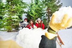 Enfants jouant des boules de neige à la forêt d'hiver Photographie stock
