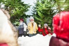 Enfants jouant des boules de neige se cachant derrière la tour de neige Image libre de droits