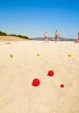 Enfants jouant des boules sur une plage Images libres de droits