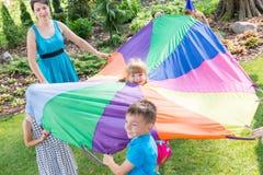 Enfants jouant des jeux de parachute photo stock