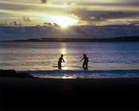 Enfants jouant en mer au coucher du soleil Images stock