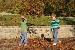 Enfants jouant en parc d'automne Photos stock