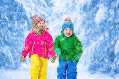 Enfants jouant en parc neigeux d'hiver Photo libre de droits