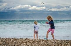 Enfants jouant en plage venteuse Images libres de droits