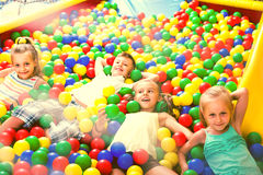Enfants jouant ensemble dans la piscine avec la boule multicolore en plastique Photo stock