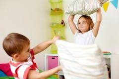 Enfants jouant et combattant par des oreillers à la maison Photos libres de droits