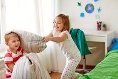Enfants jouant et combattant par des oreillers à la maison Images libres de droits