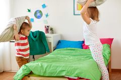 Enfants jouant et combattant par des oreillers à la maison Photographie stock libre de droits