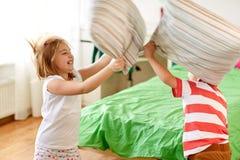 Enfants jouant et combattant par des oreillers à la maison Image libre de droits