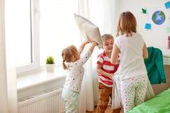 Enfants jouant et combattant par des oreillers à la maison Photographie stock
