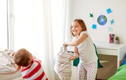 Enfants jouant et combattant par des oreillers à la maison Photo stock