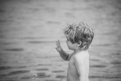 Enfants jouant - jeu heureux Main de ondulation d'enfant mignon, au bord de la mer Garçon avec le support sérieux de visage près  Images libres de droits