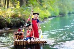 Enfants jouant l'aventure de pirate sur le radeau en bois images stock