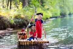 Enfants jouant l'aventure de pirate sur le radeau en bois Photo stock