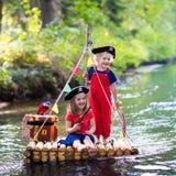 Enfants jouant l'aventure de pirate sur le radeau en bois Image stock