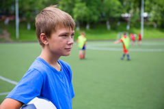 Enfants jouant le football au stade Image stock
