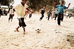 Enfants jouant le football dans la banlieue noire, Afrique du Sud Photos stock