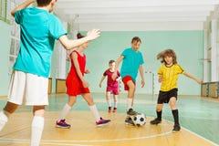 Enfants jouant le football dans la salle de gymnastique d'école Images libres de droits